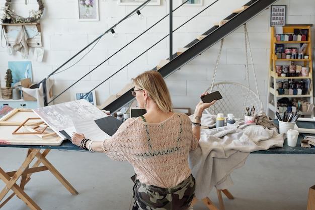 Вид сзади занятой дамы, сидящей за столом и проверяющей контракт во время работы в художественной студии