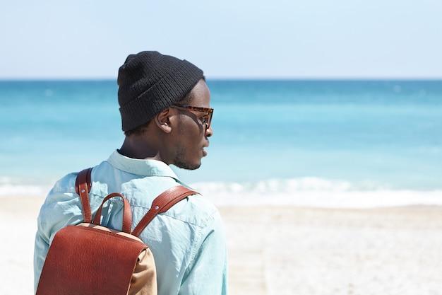 바다로 여름 휴가를 보내고 화창한 날에 놀라운 전망을 생각하면서 아름다운 푸른 바다 경치를 즐기는 가죽 배낭으로 평온한 젊은 어두운 피부 여행자의 후면보기