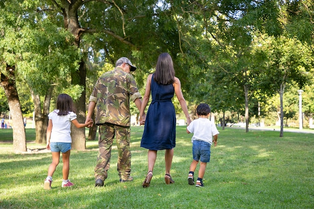 手をつないで、都市公園で一緒に歩いている白人家族の背面図。迷彩服を着たお父さん、長髪のお母さんと子供たちが自然の中で休日を楽しんでいます。家族の再会と週末のコンセプト