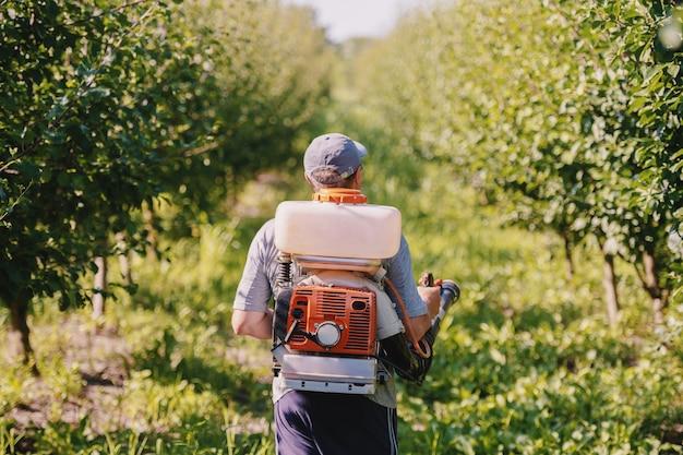 Вид сзади кавказского зрелого крестьянина в рабочей одежде, шляпе и с современной распылительной машиной для пестицидов на спине, распыляющей насекомых в саду.