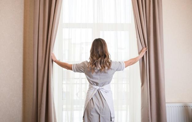 Вид сзади горничной, открывающей оконную шторку в отеле
