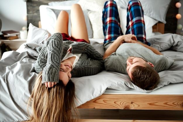 ベッドに横になっている陽気なカップルの背面図