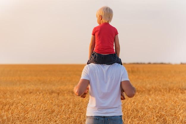 아버지 어깨에 앉아 아이의 후면 볼 수 있습니다.