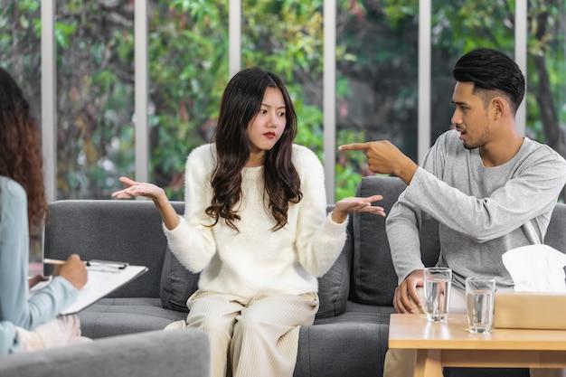 그들의 문제에 대해 논쟁하는 아시아의 젊은 연인들을 보고 듣고 있는 코치의 뒷모습,