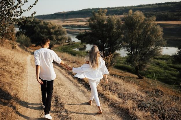 손을 잡고 아름 다운 시골에서 걷는 부부의 후면 볼 수 있습니다.