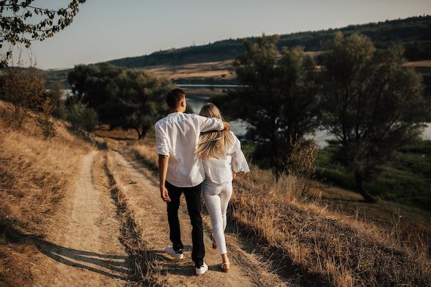 手をつないで美しい田園地帯を歩いているカップルの背面図。