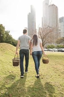 都市公園で歩くピクニックバスケットを持つカップルの後ろ姿
