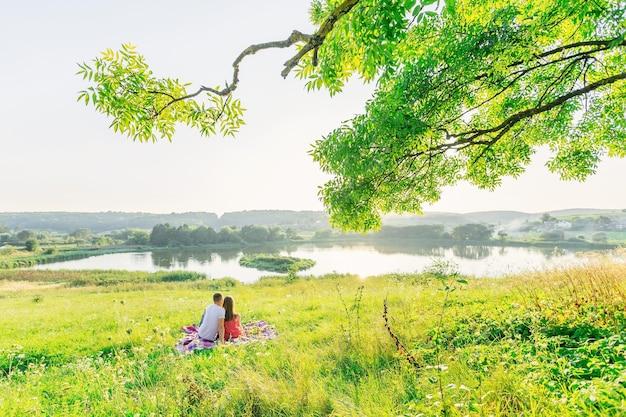 사랑에 빠진 부부의 후면 볼 수 있습니다. 남자와 여자는 담요에 앉아 호수와 숲에 감탄.