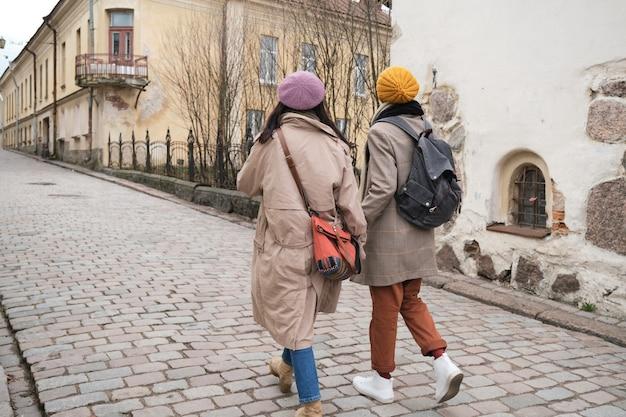 도시의 거리를 따라 걷는 두 명의 관광객의 뒷모습