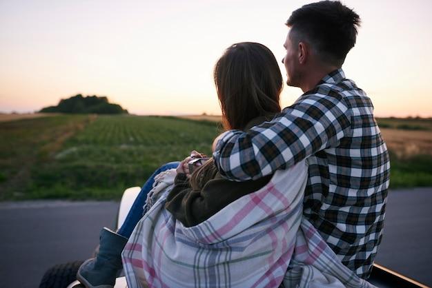 座って眺めを楽しんでいるカップルの背面図。