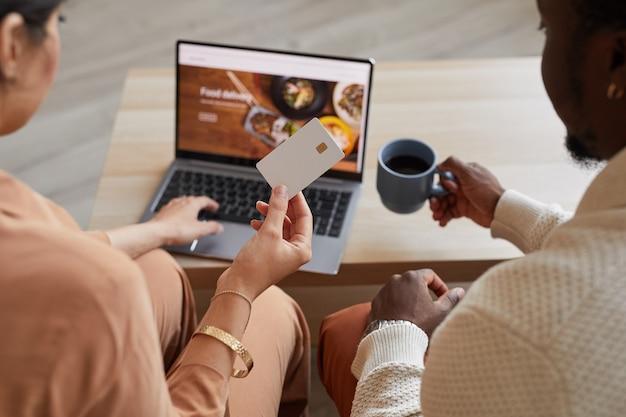 노트북 앞에 앉아 온라인 쇼핑을 위해 신용 카드를 사용하는 부부의 후면보기