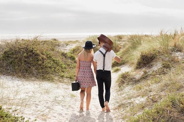 ビーチを歩いているカップルの背面図