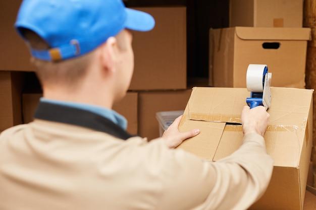 Вид сзади курьера, упаковывающего картонные коробки с липкой лентой в фургоне