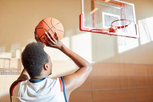 Вид сзади решительного баскетболиста, бросающего мяч в корзину