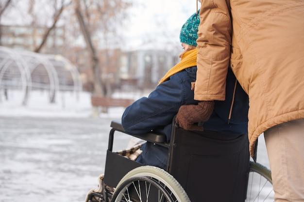 Вид сзади на женщину-инвалида, гуляющую в парке зимой со своим другом