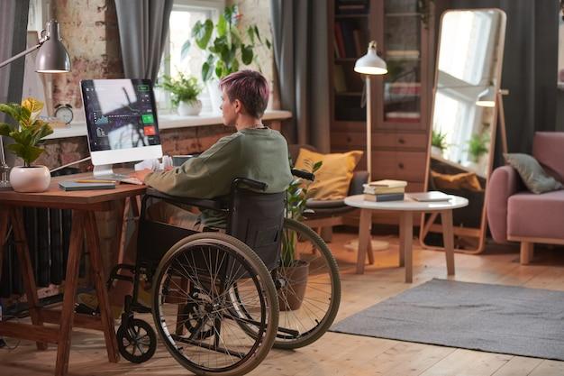 国内の部屋で新しいソフトウェアを使用してコンピューターでプログラマーとして働いている障害のある女性の背面図