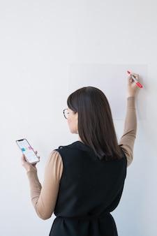 Вид сзади элегантной бизнес-леди или тренера со смартфоном, делающей презентацию на доске