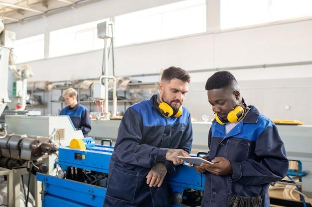 Вид сзади инженеров в рабочих шлемах, стоящих в современной мастерской и вместе изучающих производственные процессы
