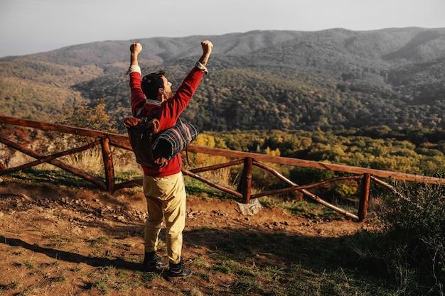 손을 제기하는 탐색기의 후면보기입니다. 아름다운 화창한 가을 날입니다. 뒷면에 배낭과 담요를 갖는 남자. 자유.