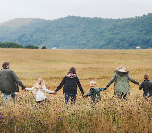 フィールドを歩いて手をつないでいる家族の背面図