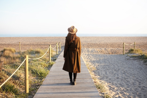 Вид сзади модной женщины с распущенными темными волосами стоял один на променаде, направляясь к морю. до неузнаваемости молодая женщина в шляпе и пальто пришла в океан, чтобы очистить голову, сталкиваясь со стрессом на работе
