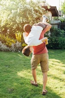공원에서 그의 아들을 들고 아버지의 뒷 모습