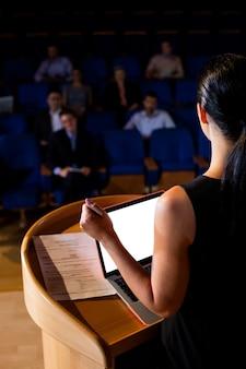 Вид сзади женского руководителя бизнеса, выступая с речью