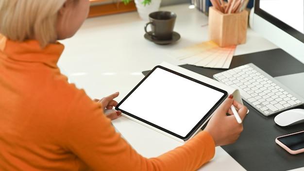 クリエイティブなオフィスに座っているときにデジタルテーブルを使用して女性デザイナーの背面図。