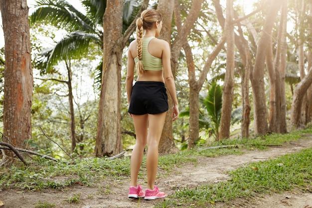 運動の体と長い三つ編みの女性のジョガーの背面図は、実行する準備をして公園の道に立っているスポーツウェアに身を包んだ。
