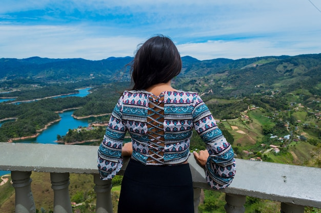 Вид сзади туристки, созерцающей природу в гуатапе, колумбия, с вершины камня пенол
