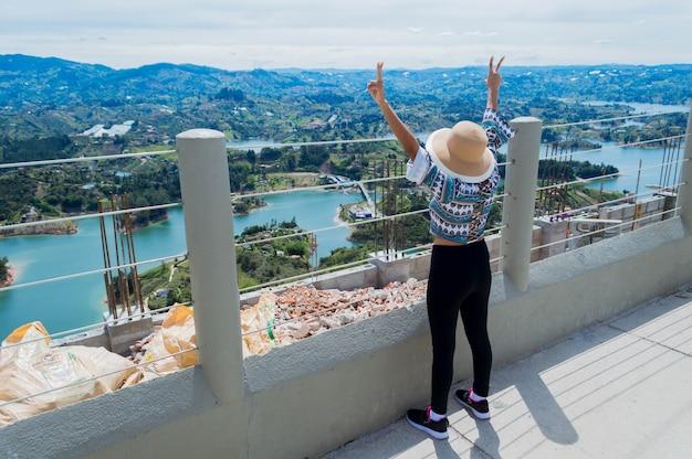 Вид сзади женщины-туристки, поднимающей руки на краю камня пенол в гуатапе, колумбия