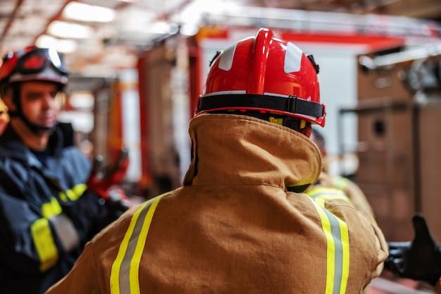 Вид сзади пожарного, надевающего защитную одежду и шлем, стоя в пожарной части.