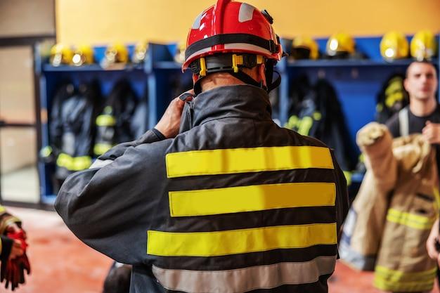 Вид сзади пожарного, надевающего защитную одежду
