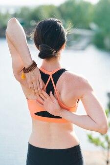 Вид сзади подтянутой женщины с пучком волос, созерцающей озеро и держащей руки вместе
