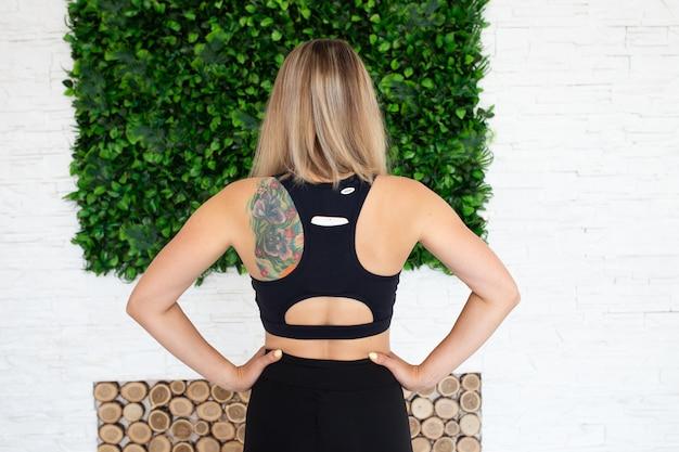 Вид сзади фитнес женщина с татуировкой
