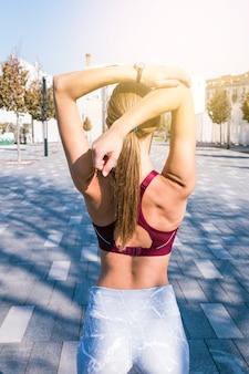 Вид сзади фитнес молодая женщина в спортивной одежде, протягивая руку
