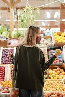 Вид сзади девушки в маске для лица, стоящей у прилавка с фруктами и смотрящей на лимон, выбирая его на рынке