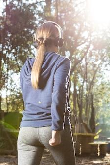 Вид сзади девушка, идущая с капюшоном и наушники