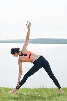 健康な体と草の上に立って、湖の岸に拡張三角形のポーズをしている精神を持つ少女の背面図