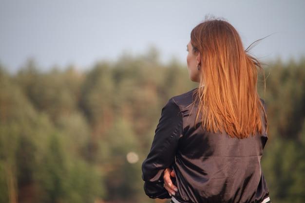 Вид сзади девушки с длинными рыжими волосами, девушка смотрит на лес, выборочный фокус
