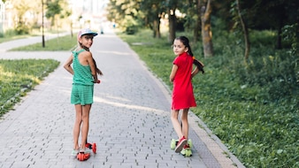 Rear view of girls riding kick scooter on pavement in the park