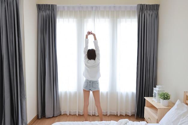 Вид сзади хорошей формы и здоровой азиатской молодой женщины просыпаются утром