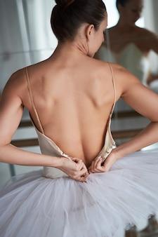 Вид сзади изящной балерины расстегивая ее костюм.
