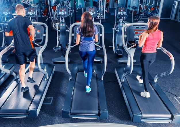Вид сзади группы друзей, тренирующихся на беговой дорожке в ярком современном тренажерном зале