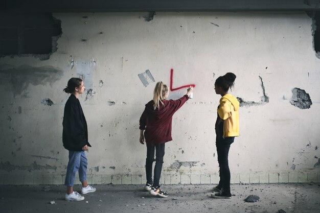 Вид сзади группы девочек-подростков, стоящих в помещении в заброшенном здании