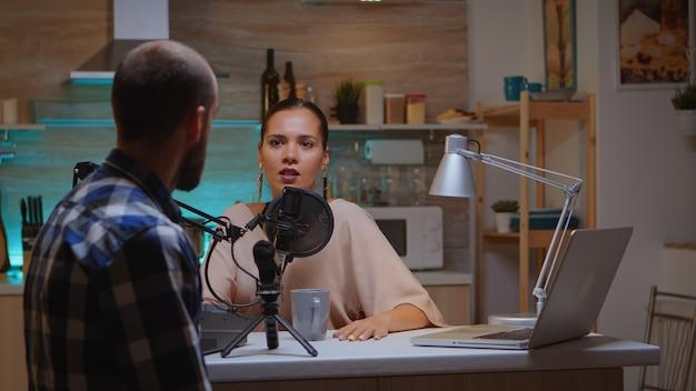 Вид сзади гостя, разговаривающего с ведущей во время ее онлайн-шоу. креативное онлайн-шоу. производство в прямом эфире. ведущий интернет-вещания, транслирующий прямой эфир, записывающий общение в цифровых социальных сетях.