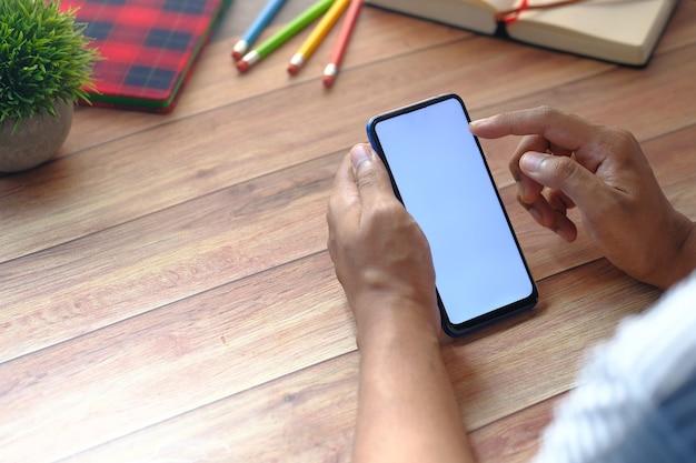 Вид сзади руки, держащей смартфон на деревянном столе