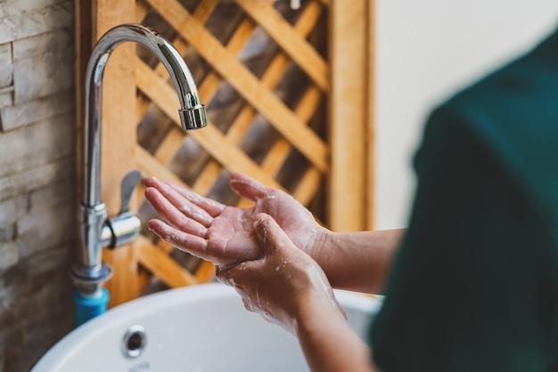 コロナウイルスパンデミック予防のためにクロム蛇口と石鹸で洗う手の背面図