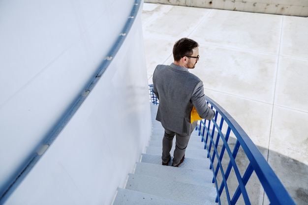 石油タンクの階段を下りて離れているハンサムな白人実業家の背面図。