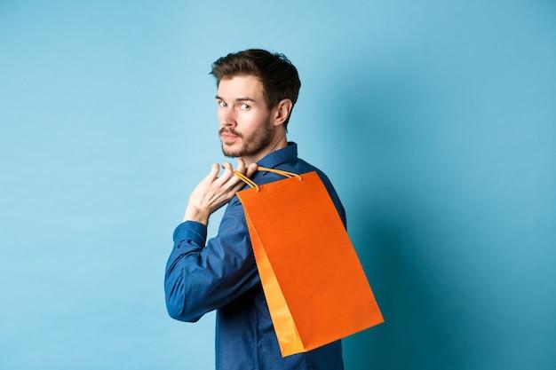 어깨에 다시 쇼핑을 들고 뒤에 파란색 배경에 서있는 행복 한 남자의 후면보기.
